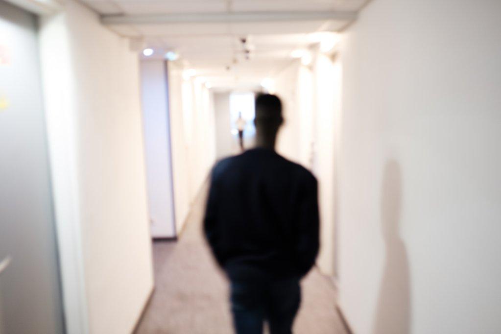 Un jeune dans le couloir de l'hôtel Milton menant aux chambres réservées au programme Passerelle. © Augustin Legall / MSF