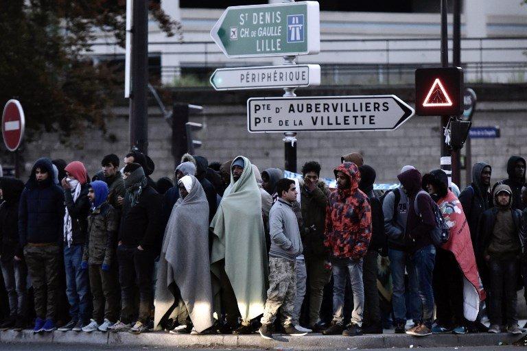 AFP/ PHILIPPE LOPEZ |Porte de la Chapelle à Paris, le 9 mai 2017, des migrants attendent d'être évacués vers des centres.