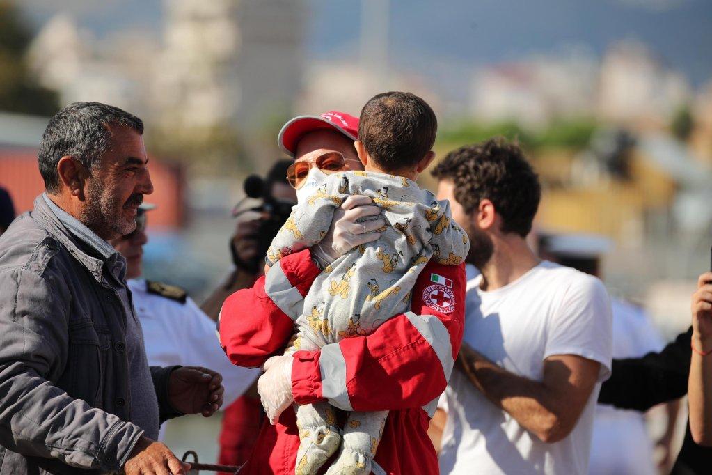 """طفل بين مهاجرين يهبطون في باليرمو من السفينة """"إس أو إس ميديتراني أكويروس"""". المصدر: أنسا/ أجو بيتيكس"""
