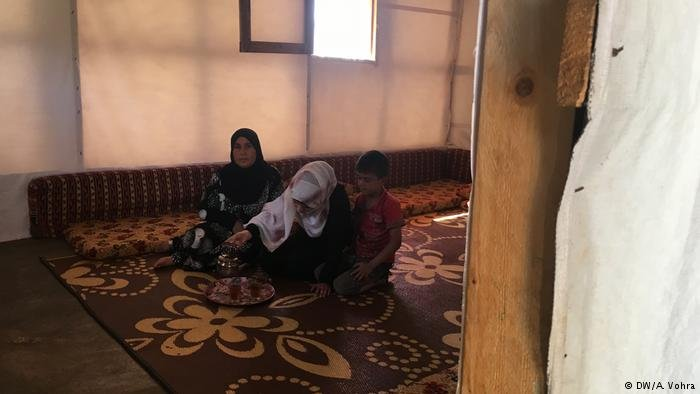 Three people sitting in a refugee camp in Lebanon