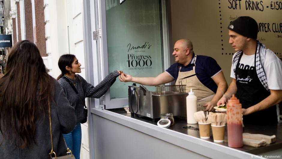Imad hands falafels to people who walk outside his restaurant | Photo: DW/M. Karakoulaki