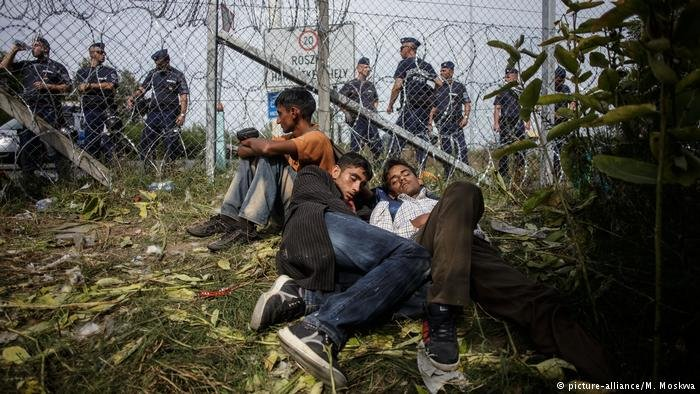 Refugees sit against a fence in Hungary, police line the other side of the fence