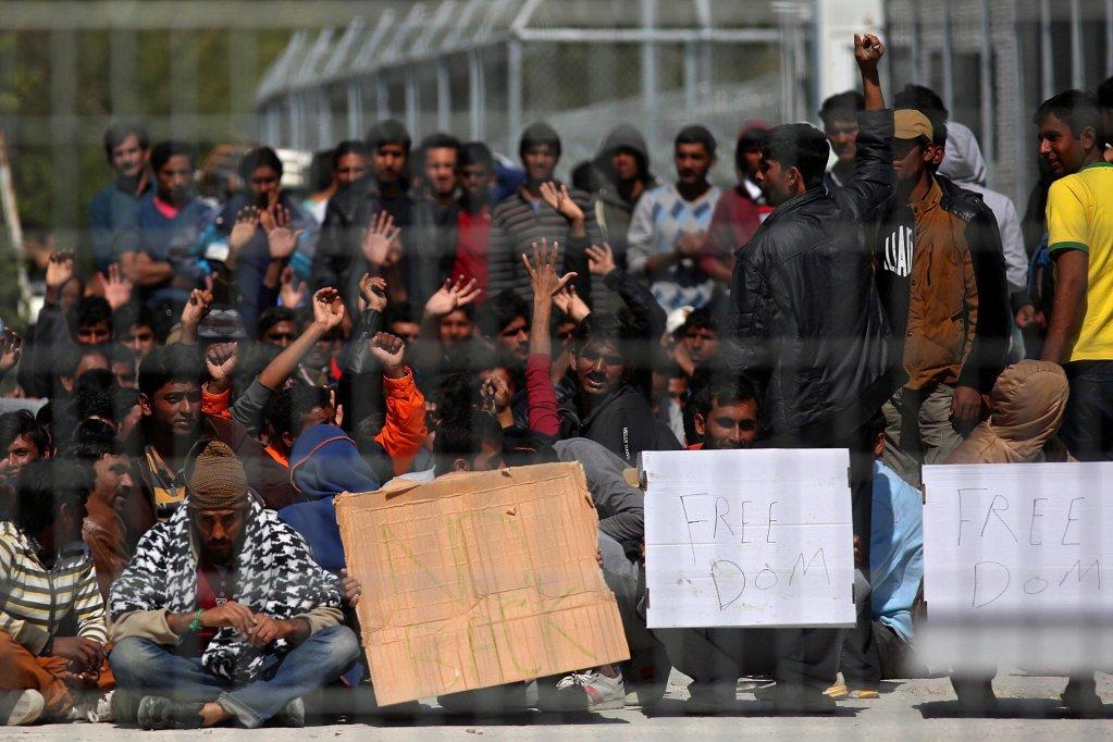 """Ansa : مهاجرون من أفغانستان وباكستان يحتجون في نقطة ساخنة، كانت مركزا للاعتقال في موريا بجزيرة ليسبوس اليونانية، على الترحيل. المصدر: """"إي بي إيه""""/ اوريستيس بانايوتي."""