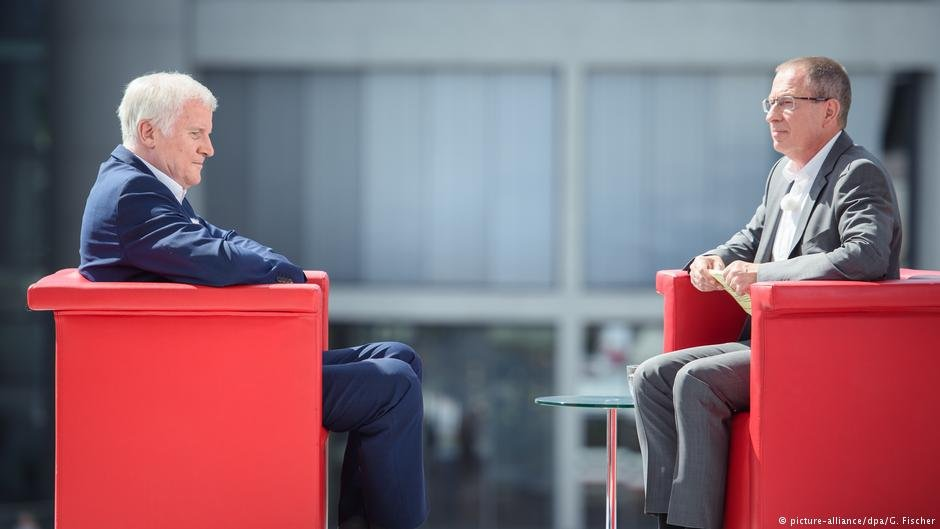 The ARD interviewer, Thomas Baumann (R), pressed Seehofer (L) for details on how more anchor centers could be opened by Nahles and Merkel