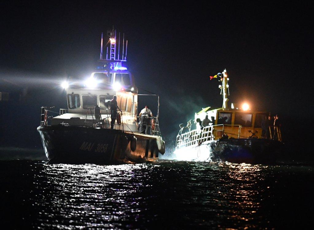 Daniel MIHAILESCU / AFP |Un bateau de la police des frontières remorquant un bateau de migrants vers le port de Midia, le 13 septembre 2017.