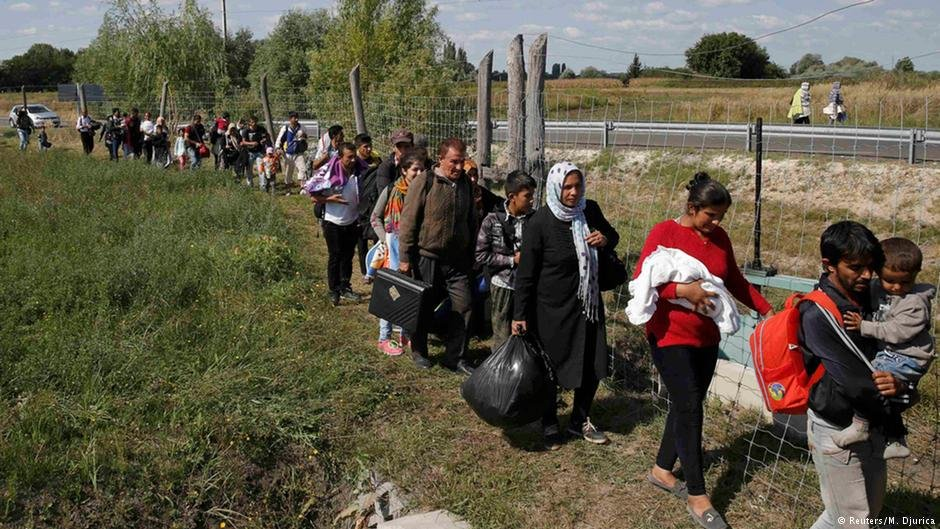 Refugees walk along a roadside fence near Roszke in 2015
