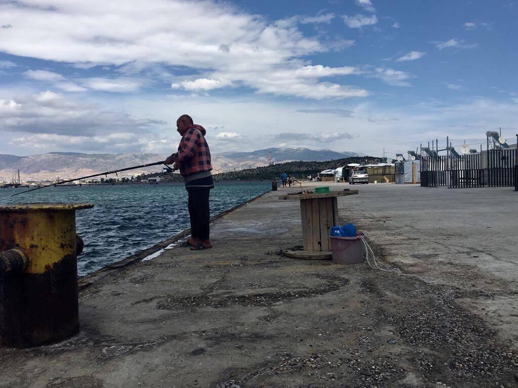 La mer borde le camp de Skaramagas. Certains en profitent pour pêcher. Crédit : Charlotte Boitiaux