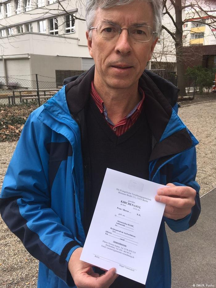 Pfarrer Jeutner zeigt einen Kirchenasyl-Ausweis der Versöhnungsgemeinde Berlin