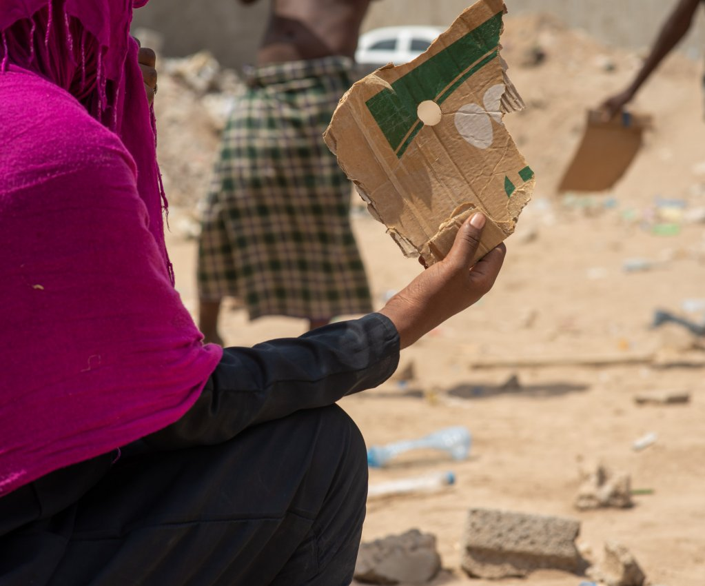 An Ethiopian woman stranded in Aden city fans herself with cardboard while sitting in the sun one of the few women among the stranded migrants  Photo IOM 2020Rami Ibrahim
