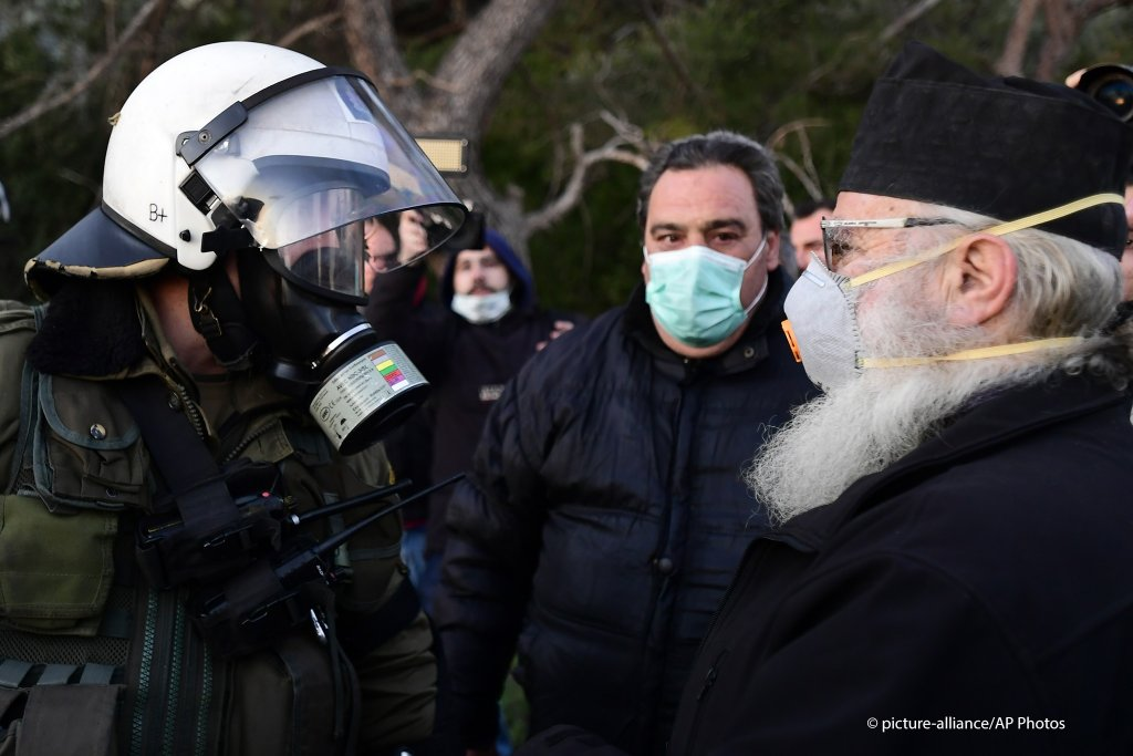 A Greek Orthodox priest stands in front of riot police in Karava near the area where the government plans to build a new migrant detention center on the northeastern Aegean island of Lesbos Greece February 25 2020  Photo picture-allianceMichael Varaklas