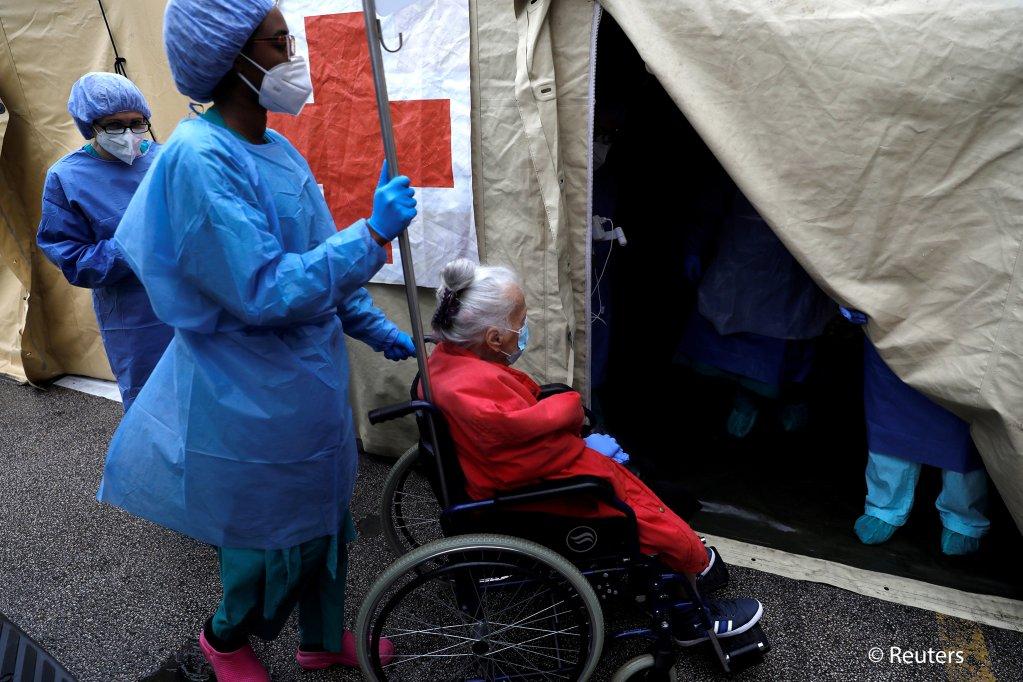 در جریان شیوع ویروس کرونا یک کارمند صحی پیرزنی بیمار را با ویلچر به یک خیمه در نزدیکی شفاخانه سانتا ماریا در لیسابون سوق می دهد. عکس: رافائل مارتانته/ رویترز