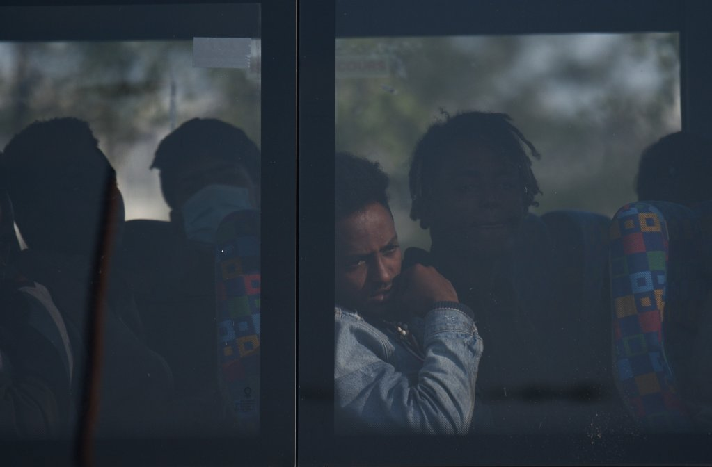 A migrant waits in the bus that will take him to a place where he can take a shower, while a police operation in underway in the Calais hospital camp.