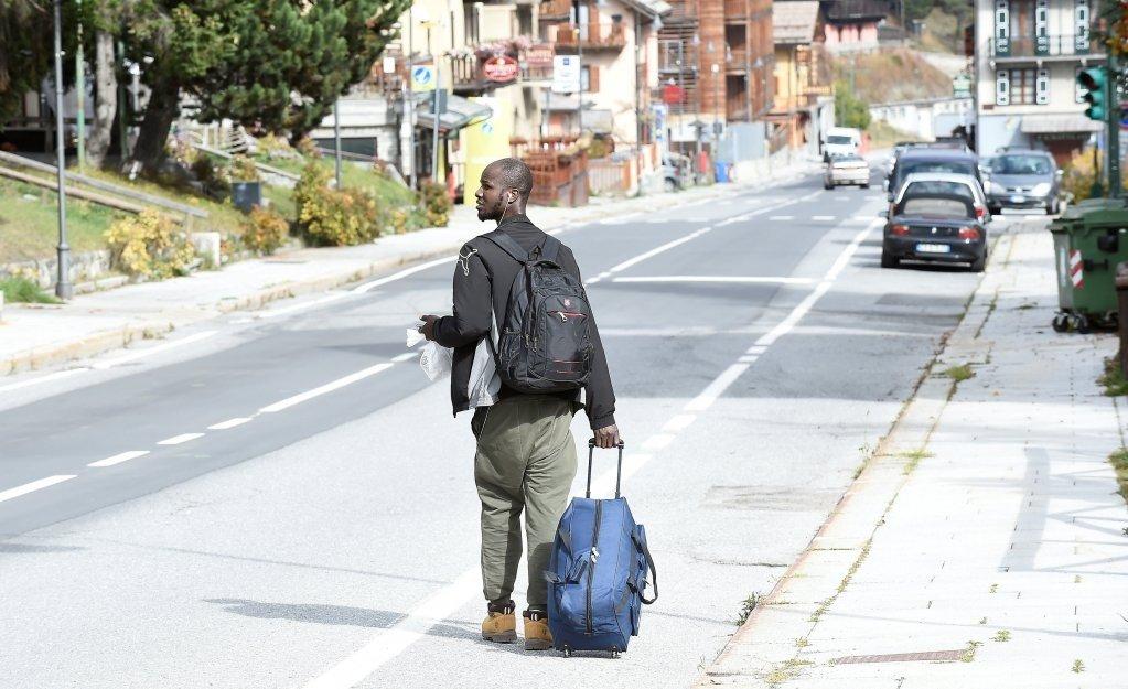 مهاجر يسير وحيدا في شوارع إحدى المدن الإيطالية على الحدود مع فرنسا. رويترز