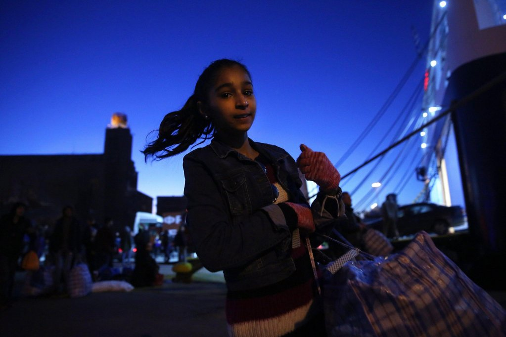 A refugee girl carries his belongings as she disembarks from the ferry 'Nissos Samos' which arrived from Lesvos Island at the port of Piraeus, Greece. Credit EPA/ ORESTIS PANAGIOTOU)
