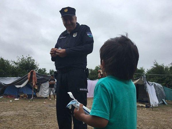 Un policier bosnien offre une friandise  une petite fille du camp de Kledusha Crdit  InfoMigrants