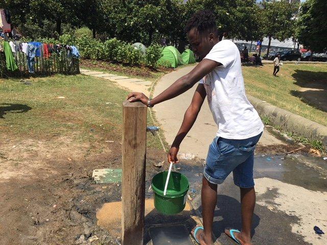 Un migrant rempli un sceau pour nettoyer ses vêtements. Crédit : InfoMigrants