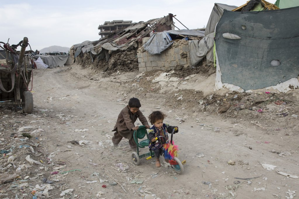 Children play along the dirt roads at an informal settlement for internally displaced people (IDPs) in Kabul. IDPs and returning refugees often struggle to get their children into school as they try to settle into a new location, often having endured trauma and loss of possessions and livelihood through flight or deportation.  Copyright: Paula Bronstein for Human Rights Watch