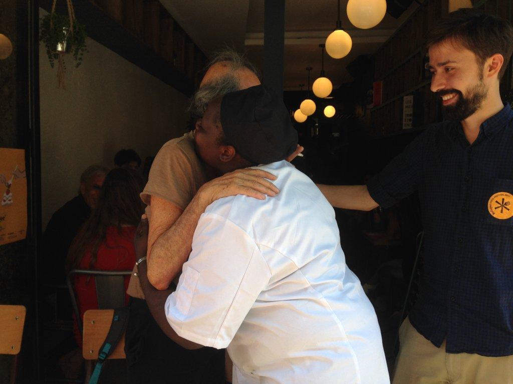Afousatou et Éric, un client, se serrent dans les bras après le repas. Crédit : Leslie Carretero