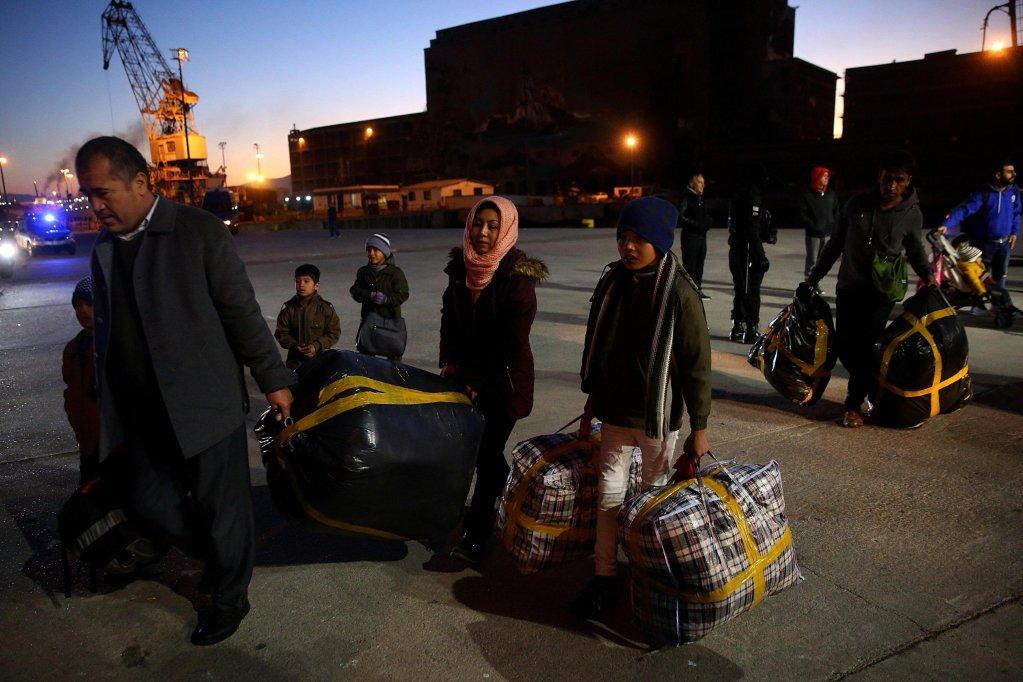 """ansa / حوالي 265 مهاجرا كانوا يقيمون في مخيم موريا يهبطون من إحدى السفن القادمة من جزيرة ليسبوس في ميناء بيروس اليوناني، وهم يحملون أمتعتهم. صورة  من أرشيف من """"إي بي إيه"""" / اوريستيس باناجيوتو"""