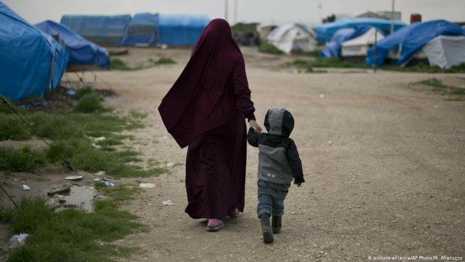 A Syrian woman holds her child as they walk through a refugee camp in northern Syria  Photo Picture-allianceAP PhotoMAlleruzzo