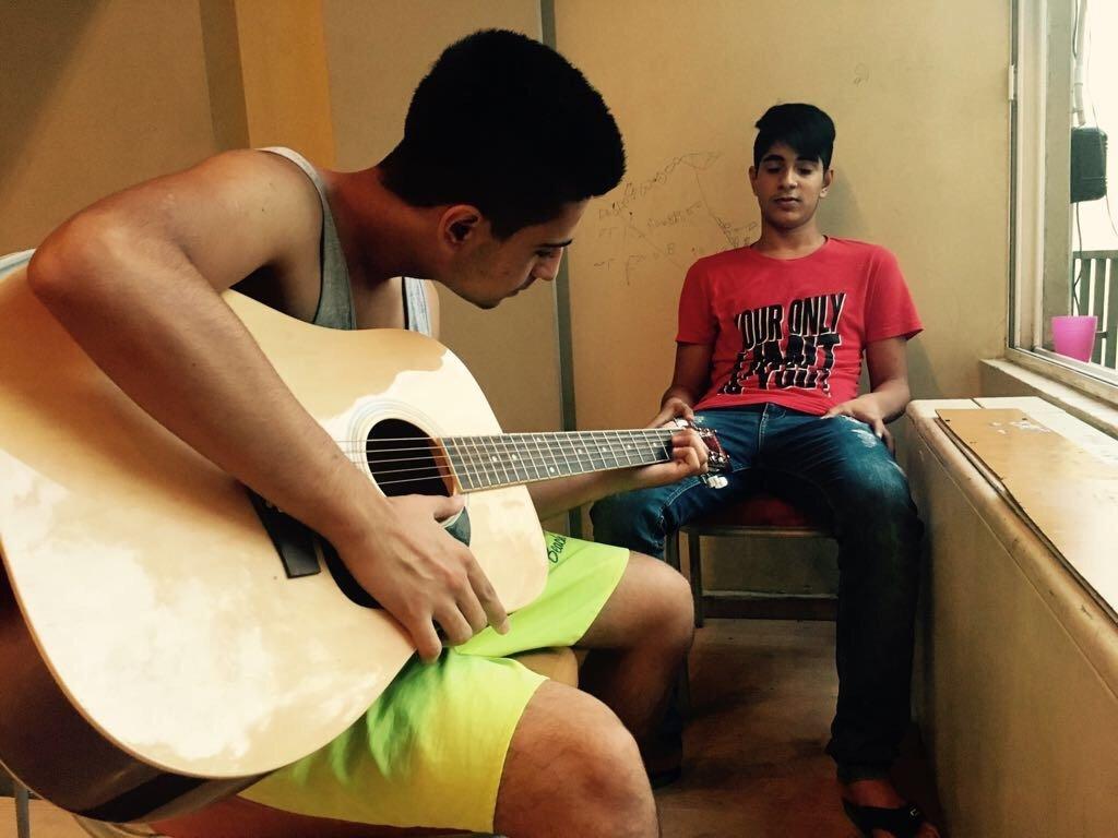 دو نوجوان مهاجر هنگام آموزش گیتار. عکس از مهاجر نیوز.