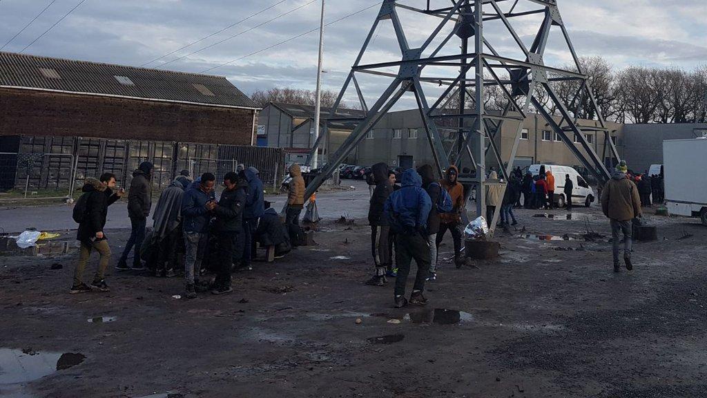 Des migrants attendent la distribution de nourriture, rue des Verrotières, à Calais.  Crédit : InfoMigrants