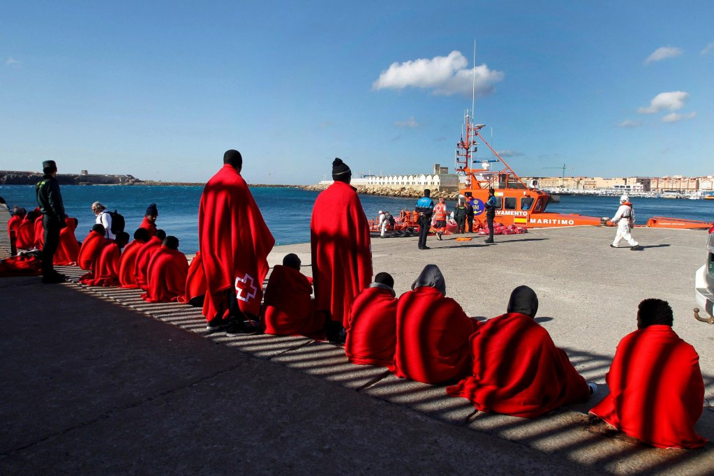 Migrants cover themselves with blankets given by the Red Cross as they wait for their transfer at the port of Tarifa, in the province of Cadiz, southern Spain. EPA/A.CARRASCO RAGEL