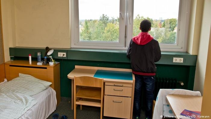 Boy looking out a window in a reception center