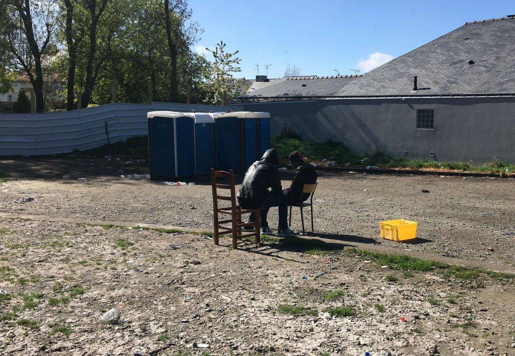 Des migrants discutent dans la cour du gymnase, non loin des toilettes installées par la mairie. Crédit : InfoMigrants