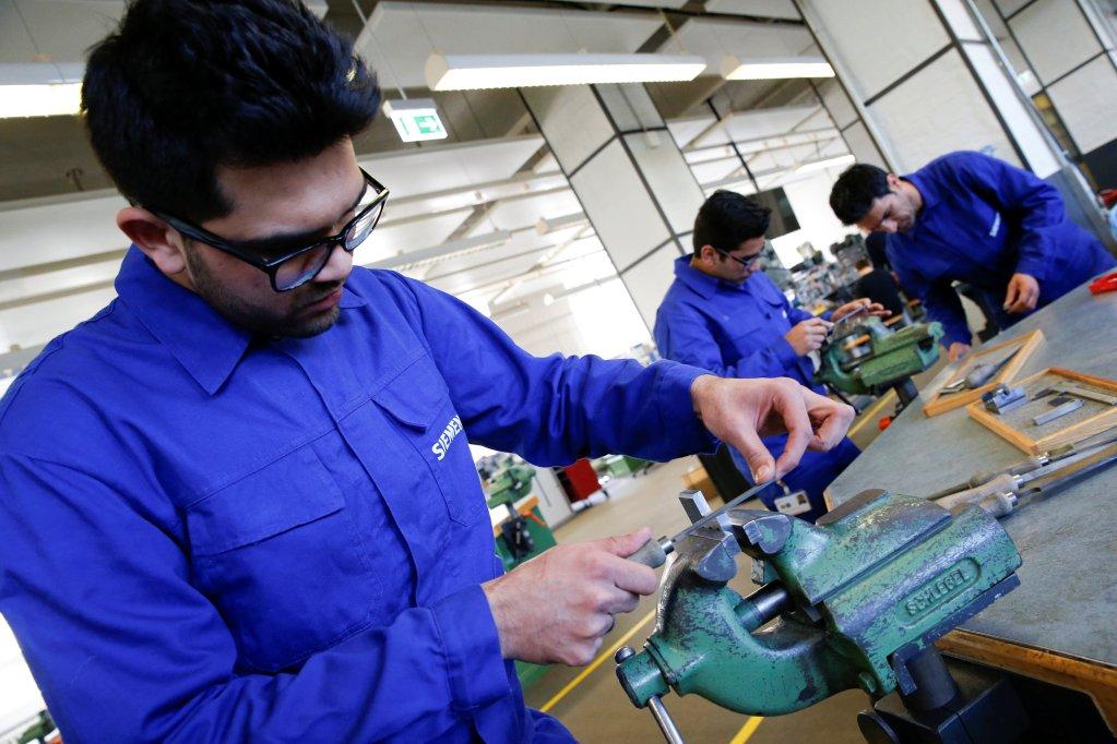 REUTERS/Fabrizio Bensch/File Photo |Des réfugiés travaillent dans un atelier du groupe Siemens, à Berlin, le 21 avril 2016.