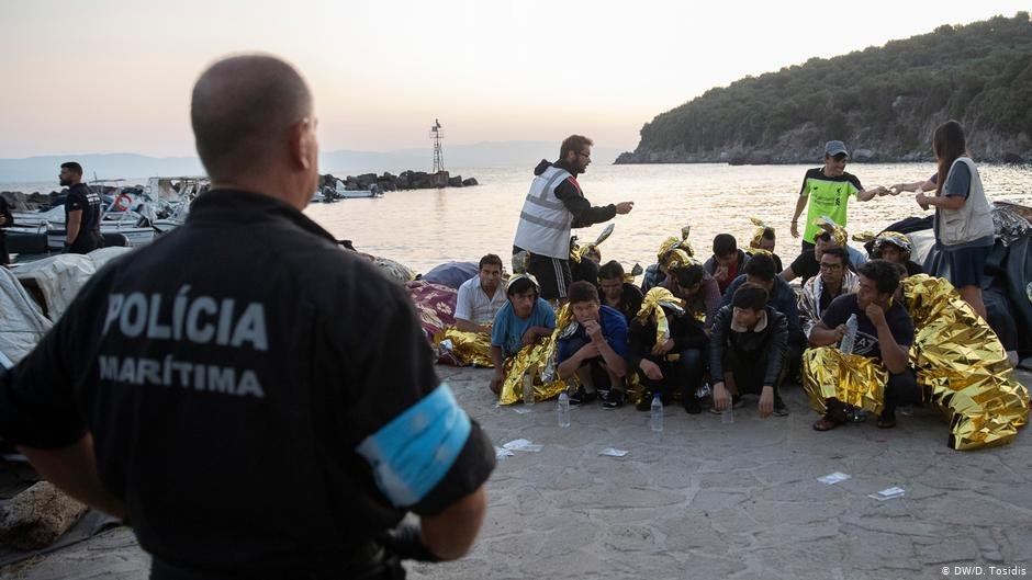 A policeman at the docks in Lesbos supervising a group of refugees  Photo DWD Tosidis