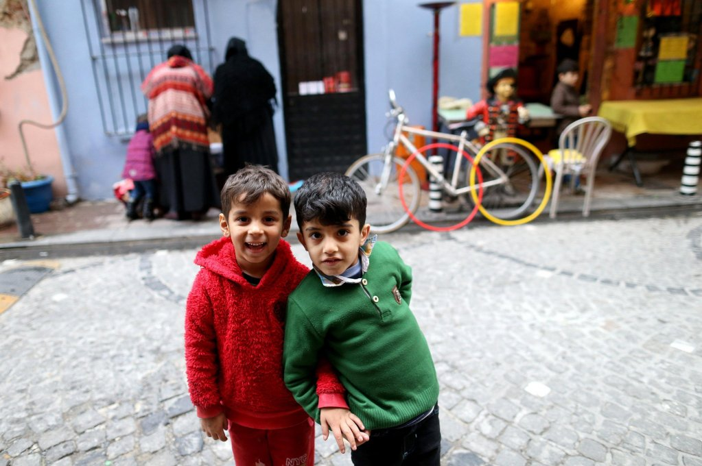 Syrian refugee children pose as their mothers check free clothes baskets on the street of the historical neighborhood of Balat, Istanbul, Turkey | Photo: EPA/ERDEM SAHIN