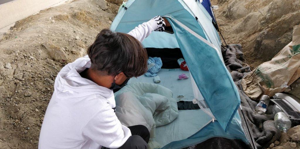 شاب يشير إلى داخل خيمته حيث ينام مع صديق. المصدر: مهاجرنيوز