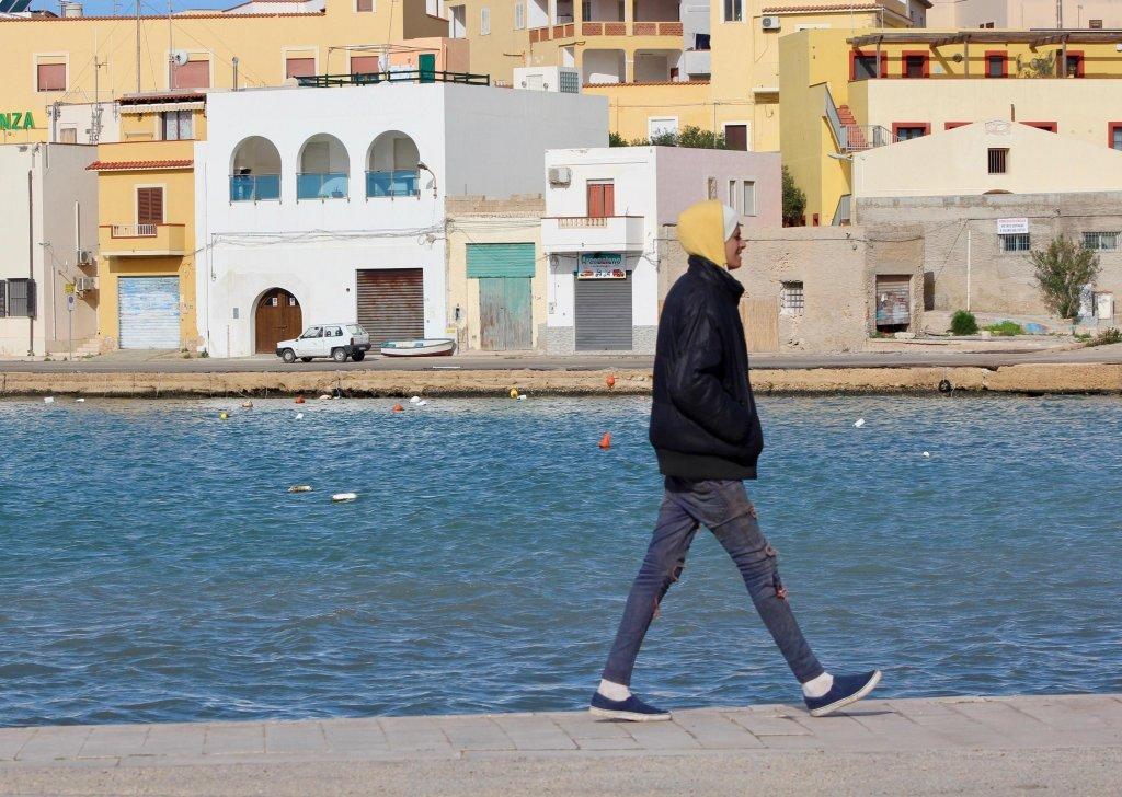 A Tunisian migrant walking on Lampedusa | Credit: ANSA/Francesco Solina