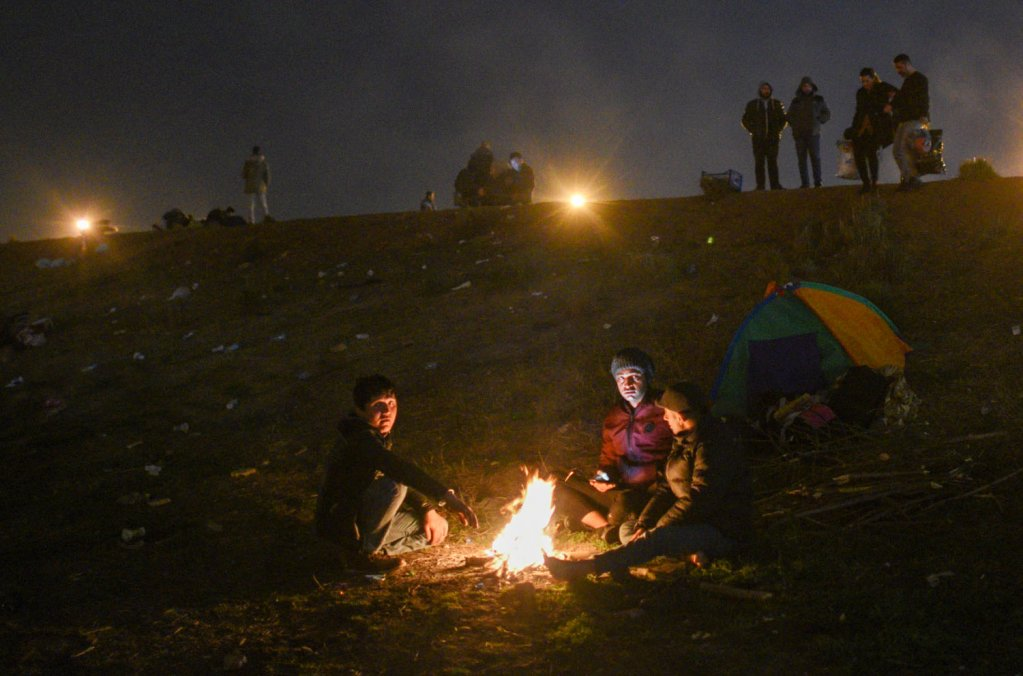 Iranian and Pakistani migrants  warm themselves around a fire near the old Edirne bridge, March 2020 | Photo: Mehdi Chebil
