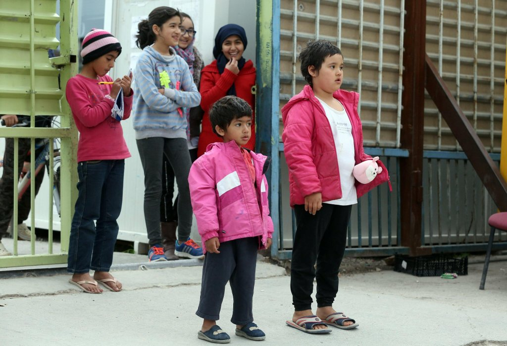 ANSA / أطفال يقفون في مدخل مخيم للاجئين في إليوناس باليونان. المصدر: إي بي إيه/ سيميلا بانتزارتزي.