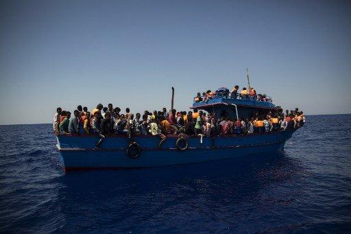 Angelos Tzortzinis / AFP |Un bateau de migrants attend d'être secouru par l'«Aquarius» de SOS Méditerranée et MSF au large de la Libye, le 2 août 2017. Depuis, les ONG ont interdiction de naviguer au large des côtes libyennes.