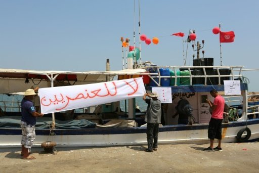 """صيادون تونسيون يعلقون لافتات مناهضة لوصول سفينة """"سي ستار"""" التي تكافح تهريب المهاجرين إلى أوروبا في 6 آب/أغسطس 2017 في مرفأ جرجيس في جنوب شرق تونس"""
