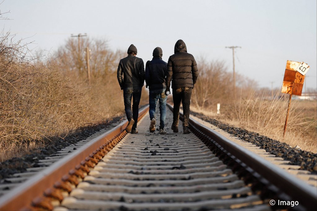 Migrants walk on a train rail at a farming area near the Evros River in Greece, on March 4, 2020 | Photo: Imago Images