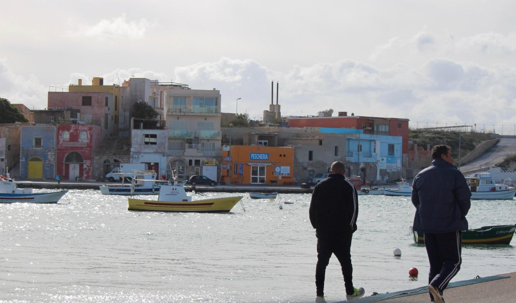 unisian migrants walking near the Lampedusa harbour. Credit: Elio Desiderio/ANSA