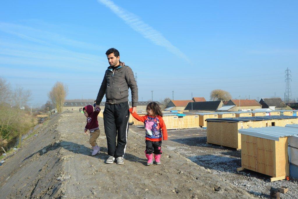 تصویر یک پناهجو با افراد خانوادهاش در اردوگاهی در کاله در شمال فرانسه، عکس از مهدی شبیل