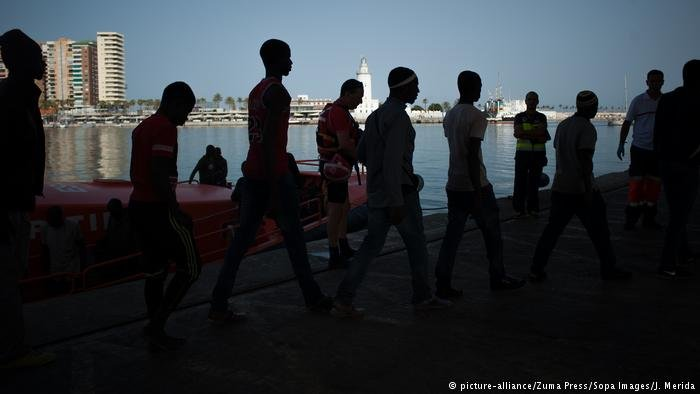 Migrants walking to a Red Cross tent in Spain