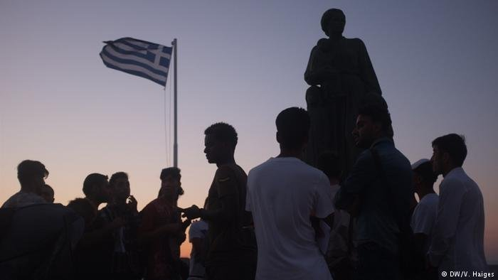 Asylum seekers stand in front of a Greek flag and a statue on Lesbos