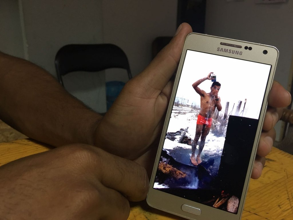 Abdul Saboor montre une photo de lui en train de se douche, à Belgrade, pendant l'hiver 2017. Crédit : InfoMigrants