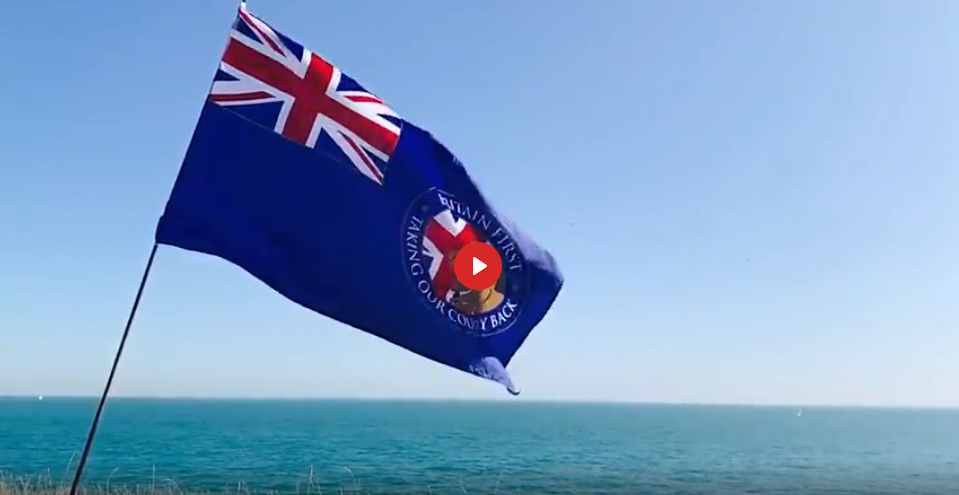 A picture of the Britain First flag waving from the cliffs above the Channel between the UK and France | Screenshot from a Britain First video