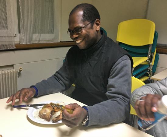 Le père William se joint aux demandeurs d'asile pour le dîner. Crédit : InfoMigrants