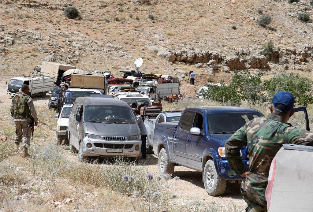 REUTERS/Hassan Abdallah |Des membres du Hezbollah escortent les réfugiés syriens souhaitant rentrer au pays. Région frontalière d'Ersal, au Liban, le 12 juillet 2017.