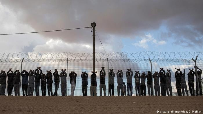 African asylum seekers and inmates of Israel's Holot Detention center stand at the fence of the facility during a 2014 protest