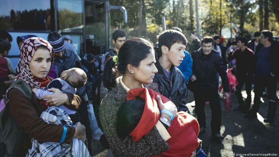From file migrants arrive by bus at an asylum seeker center on the Austrian border