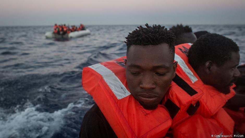 Refugees and migrants sit on a rescue boat after being pulled from  the sea off Italy